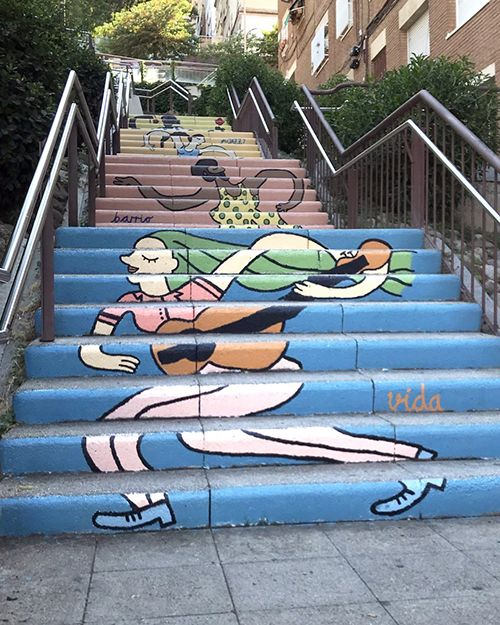An outdoor mural painted on the risers of a long staircase. Mural is of a woman playing guitar