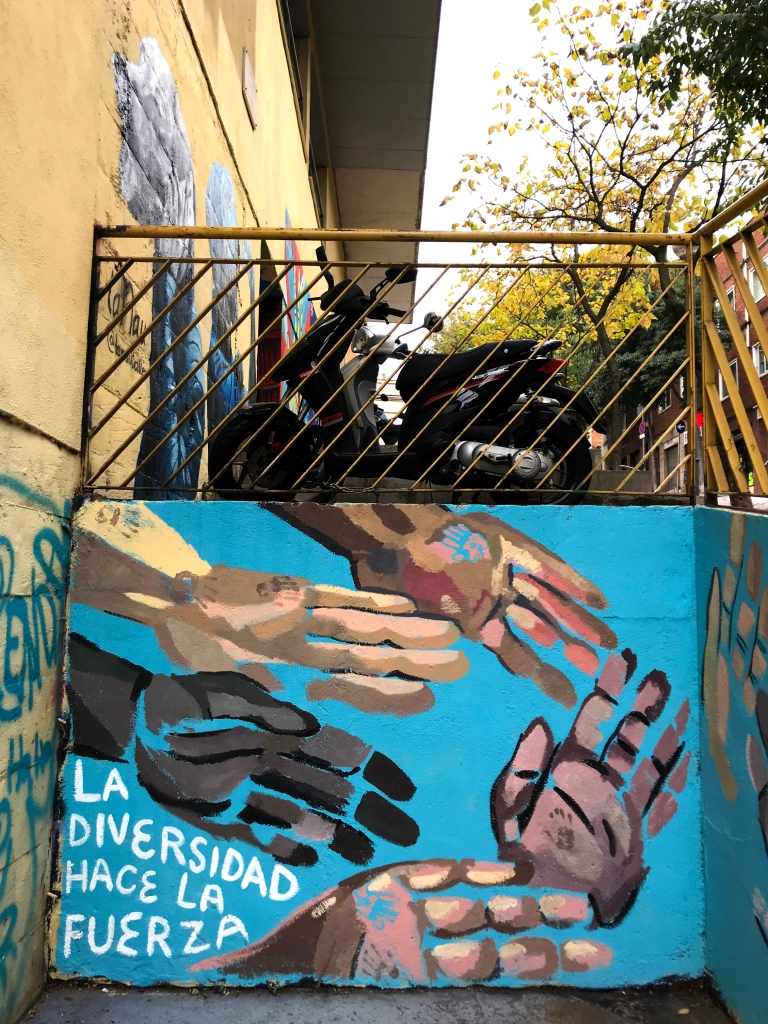 "mural of many hands painted on blue wall. white text reads, ""la diversidad hace la fuerza"""