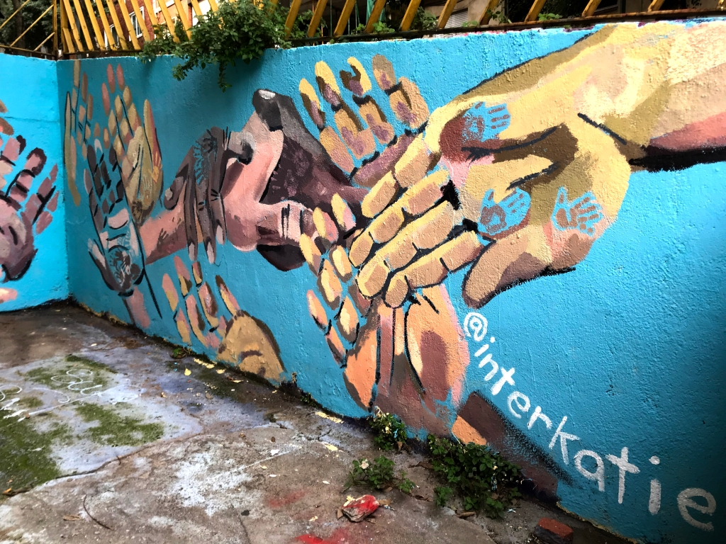 "mural of many hands painted on blue wall. white text reads: ""@interkatie"""