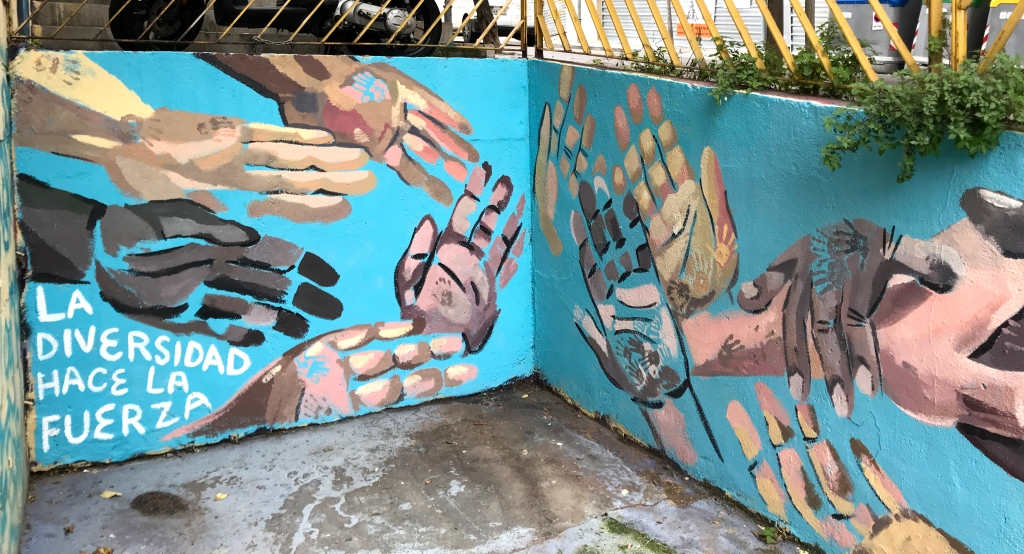 mural of many hands painted on blue wall