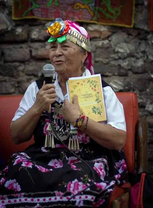 Mujer Mapuche con el libro Del Cuerpo a las Raices