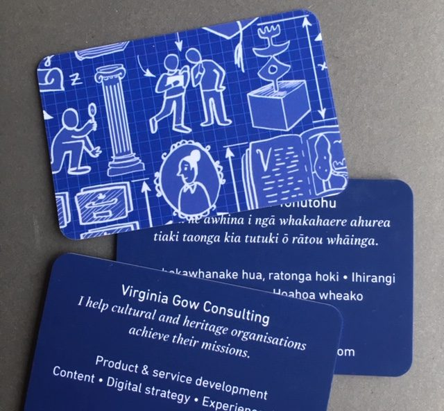 Blue business cards with a blueprint-like illustration of museum artifacts and visitors