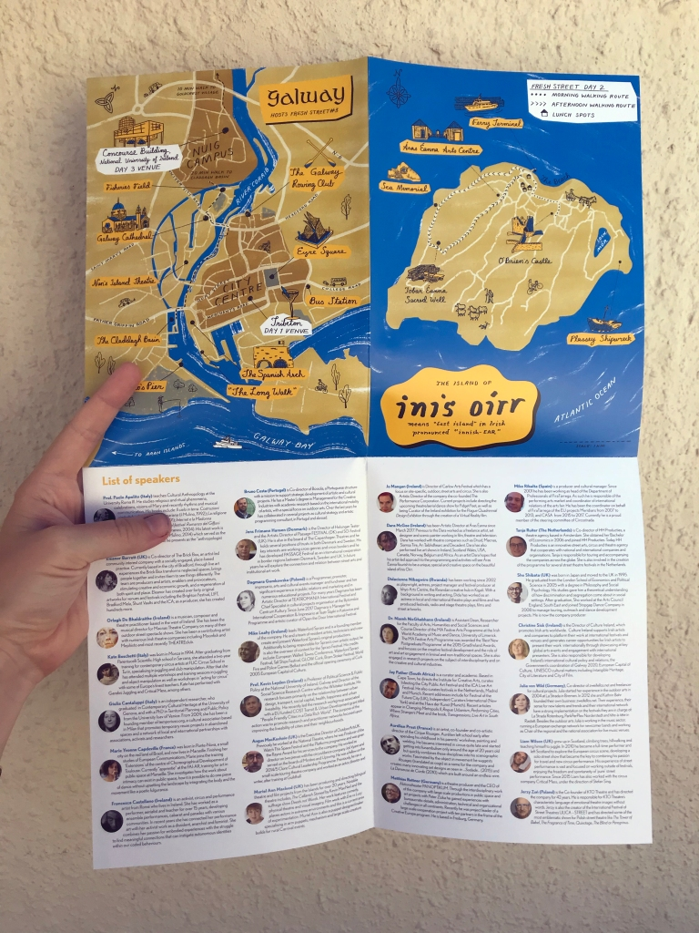 hand holding a fold-out pamphlet with two maps and headshots of conference speakers