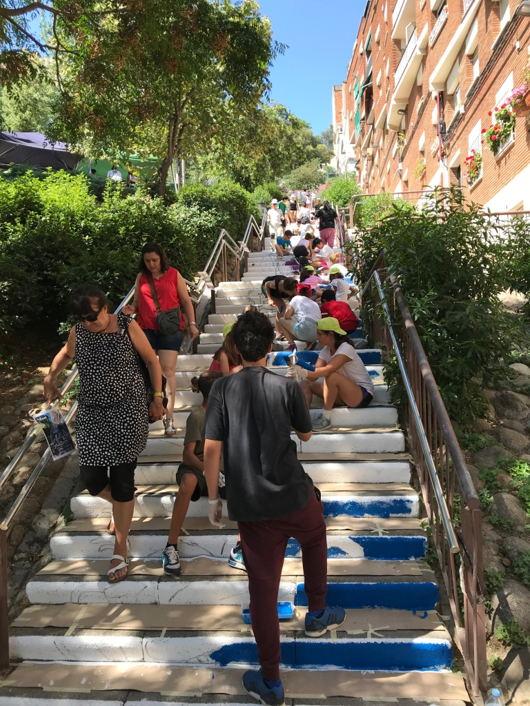 Many schoolchildren on an outdoor staircase, painting the risers of the steps