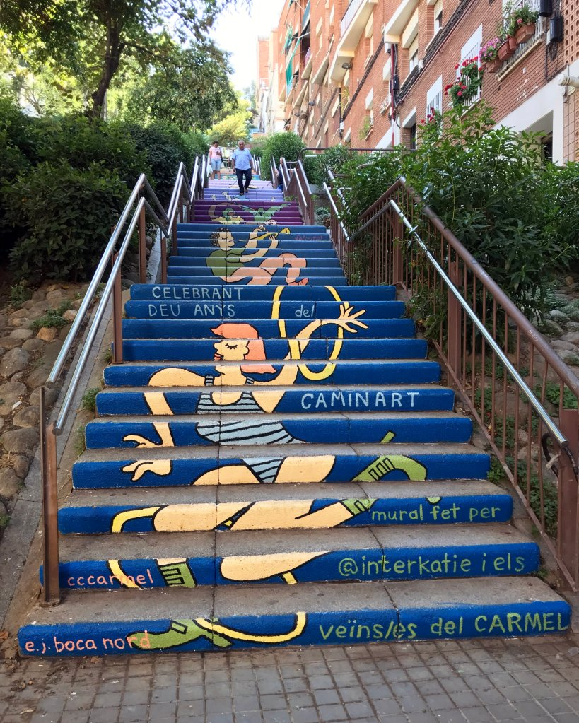 An outdoor staircase of over 150 steps, with the risers of each step painted in a colorful mural. Text reads: DEU ANYS DEL CAMINART